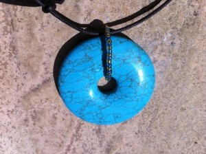 The pendant is turquoise and the seed beads are gold and blue